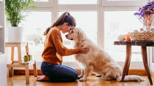woman hugging her dog in her home