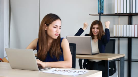 woman making a face while her coworker looks excited