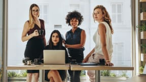 four women around a desk