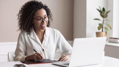 Woman taking notes while smiling at laptop.
