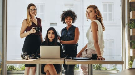 four women around a desk
