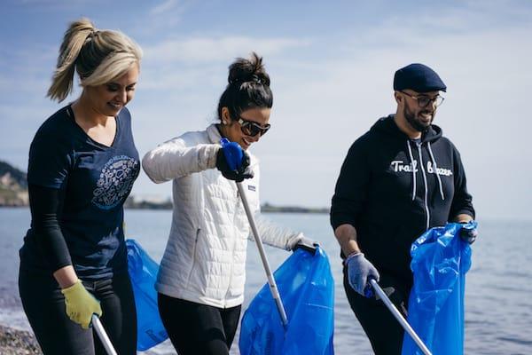 Three employees clean up a beach