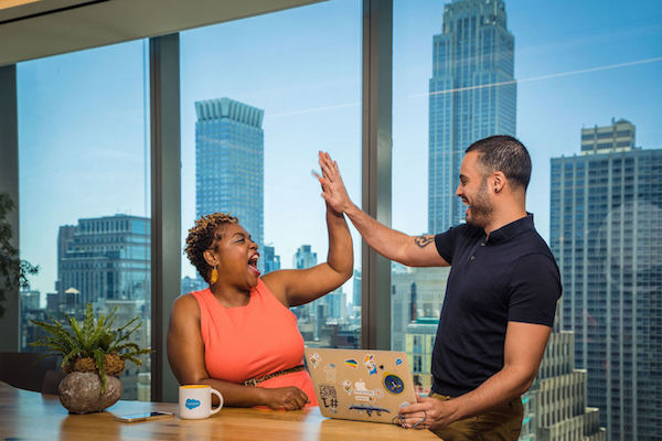 Two employees hi-five each other at Salesforce